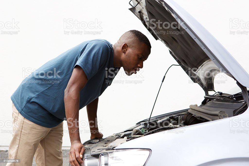 African guy looking under hood of broken down car stock photo