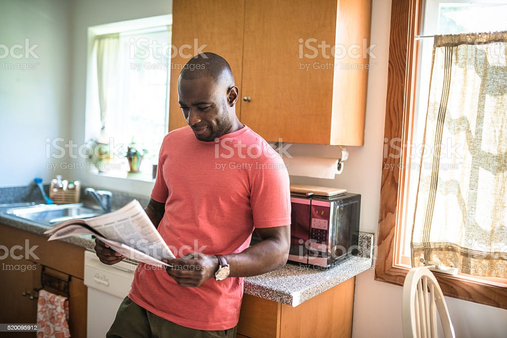 african guy reading the newspaper on the kitchen stock photo