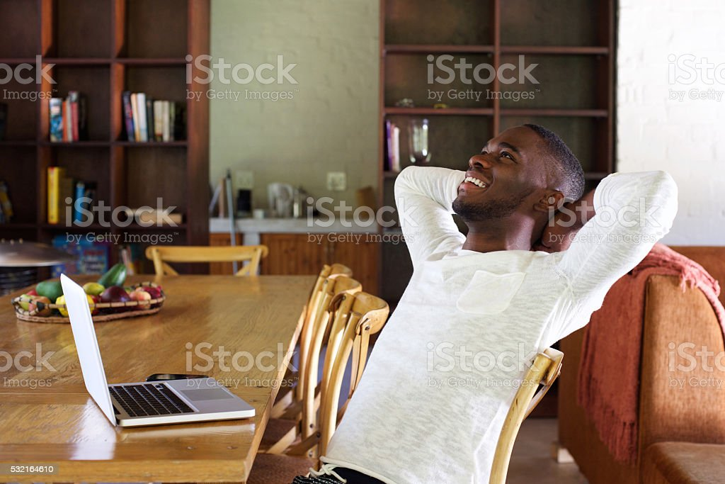 African guy relaxing at home with a laptop on table stock photo