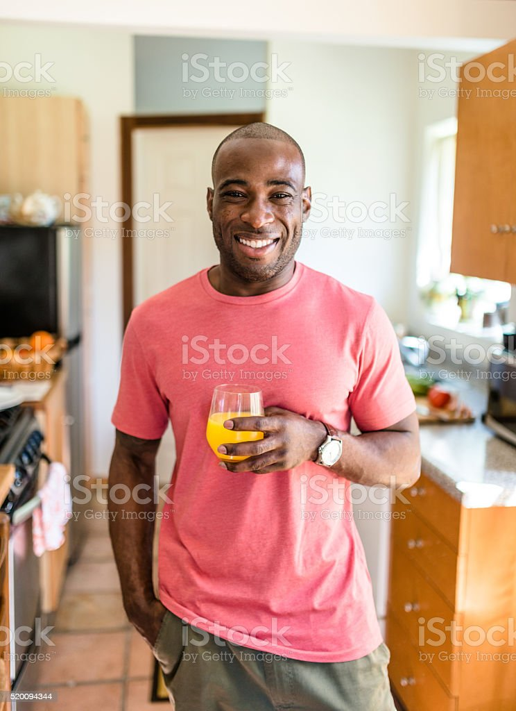 african guy smiling drinking orange juice stock photo