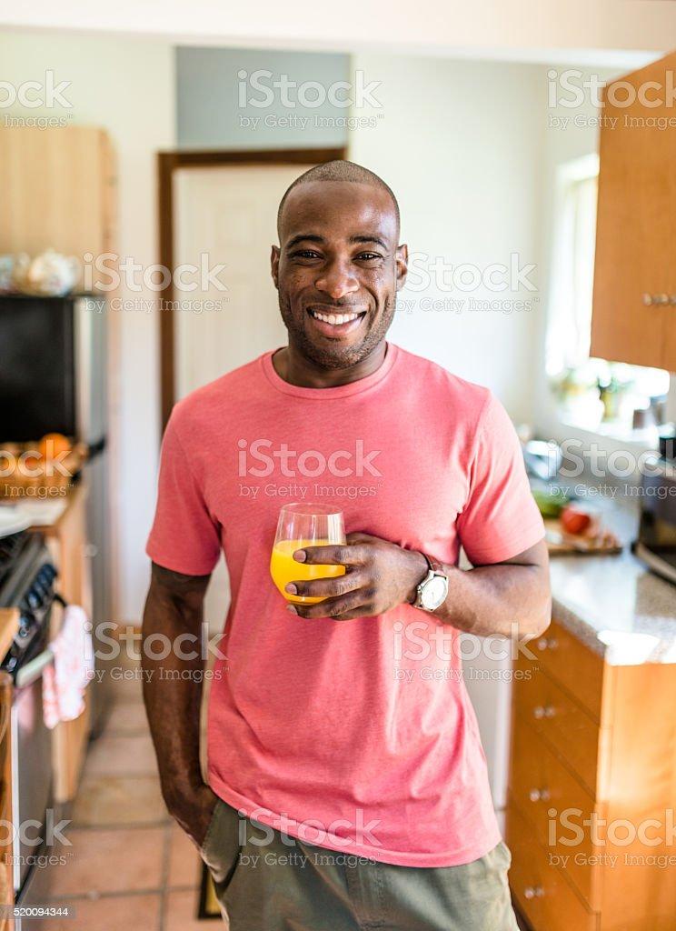 african guy smiling drinking orange juice stock photo