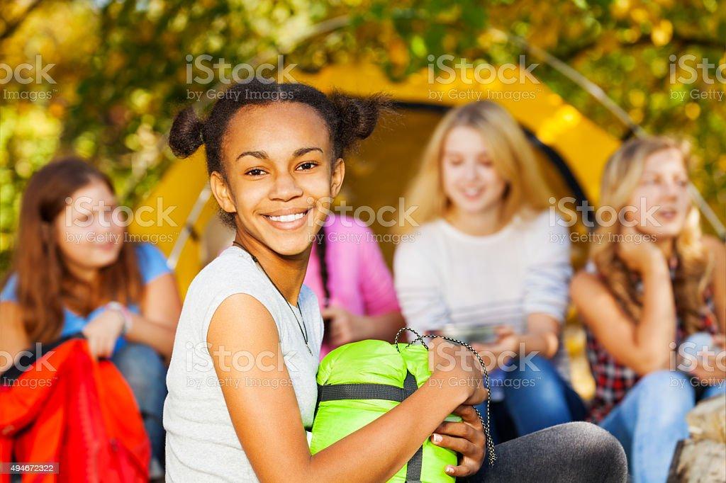 African happy girl holding green sleeping bag stock photo