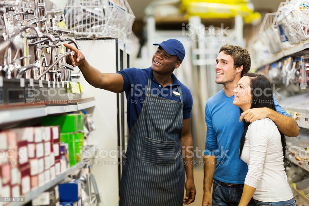 african hardware store assistant helping customers stock photo