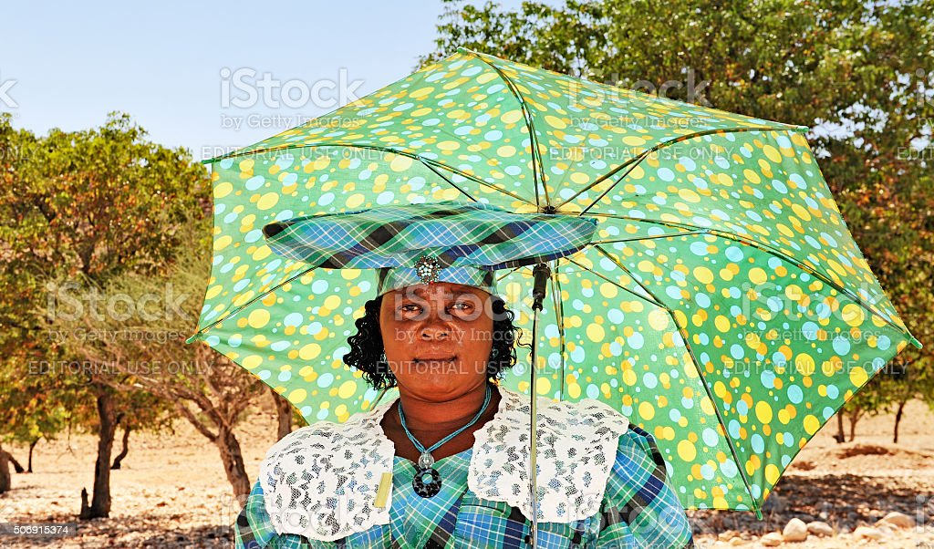 African Herero woman with  umbrella,traditional headdress and clothing,Namibia stock photo