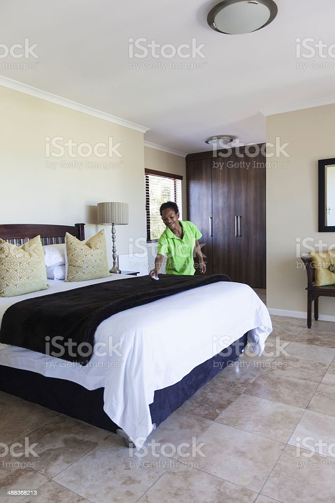 African house keeper making sure the room is tidy stock photo