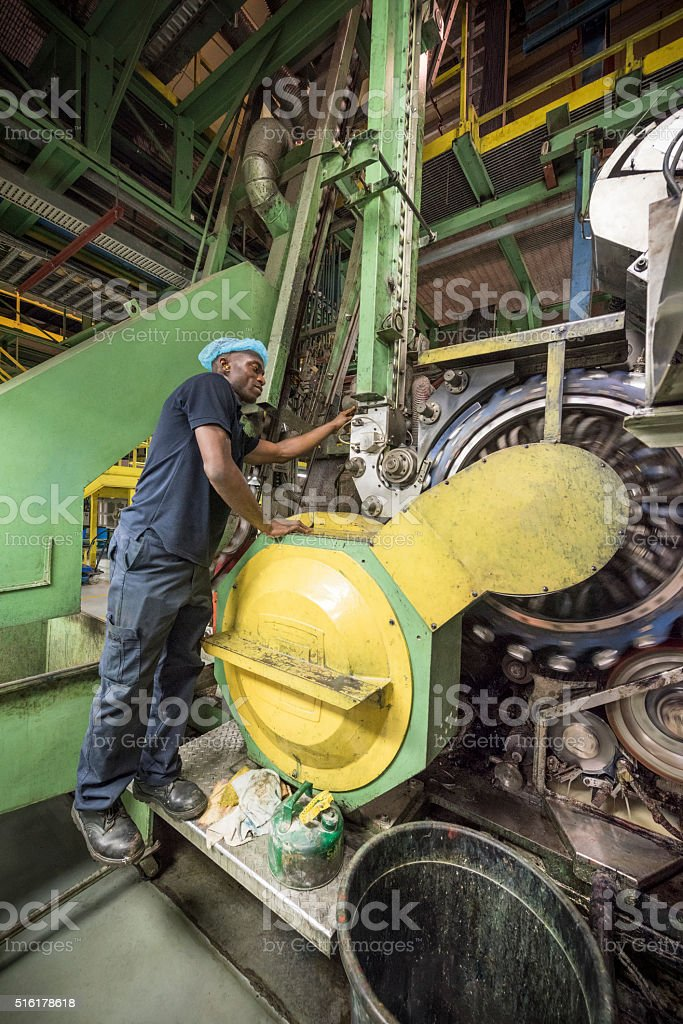 African industrial worker inspecting machine in aluminium processing plant stock photo
