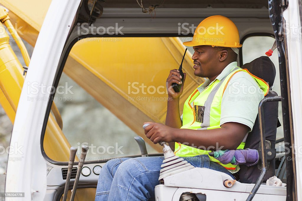 african industrial worker operating bulldozer stock photo