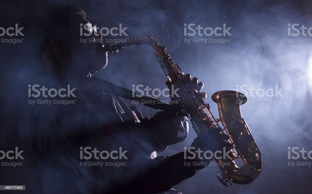 African jazz musician plays saxophone with smoke stock photo