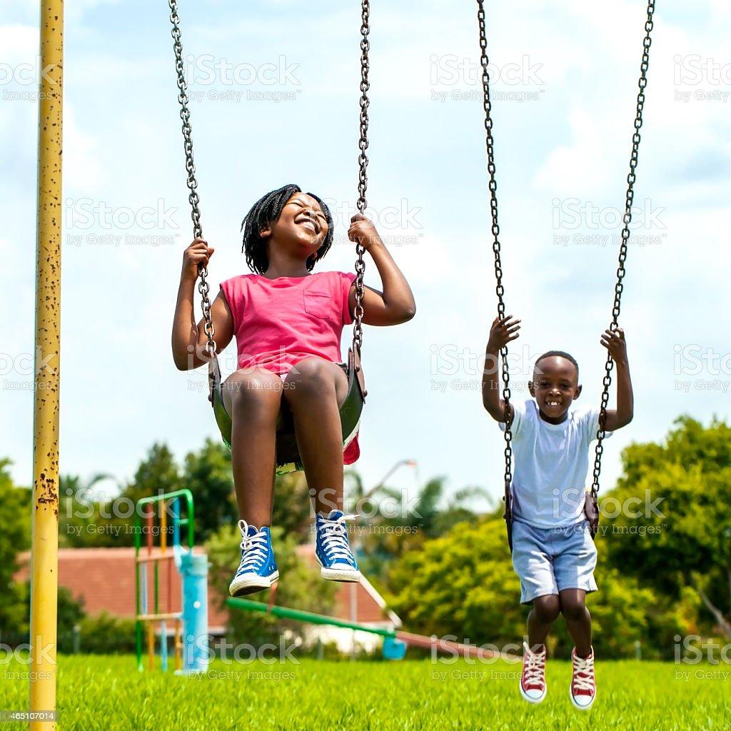 African kids having fun swinging in park. stock photo