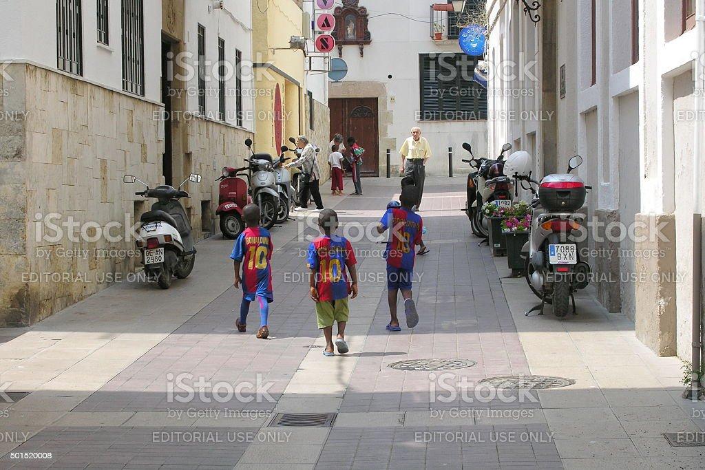 African kids play soccer at street, Tossa de Mar, Spain. stock photo