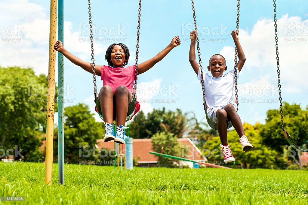 African kids playing on swing in neighborhood. stock photo
