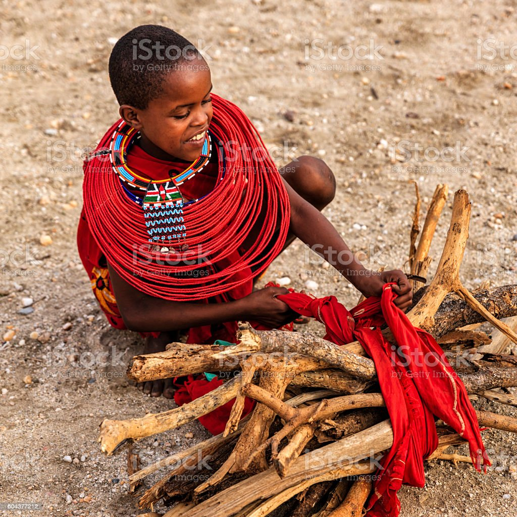 African little girl carrying brushwood on savanna, Kenya, East Africa stock photo