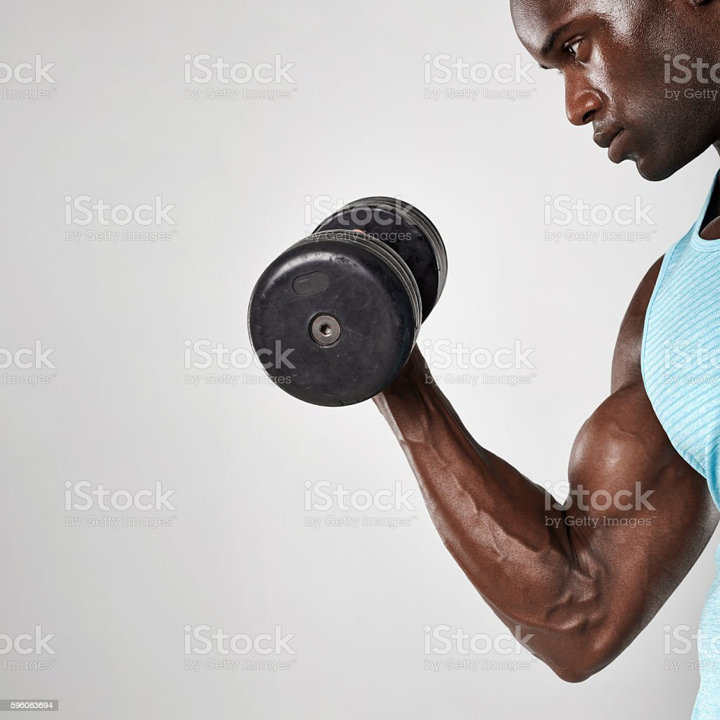African man doing biceps curl with dumbbell stock photo