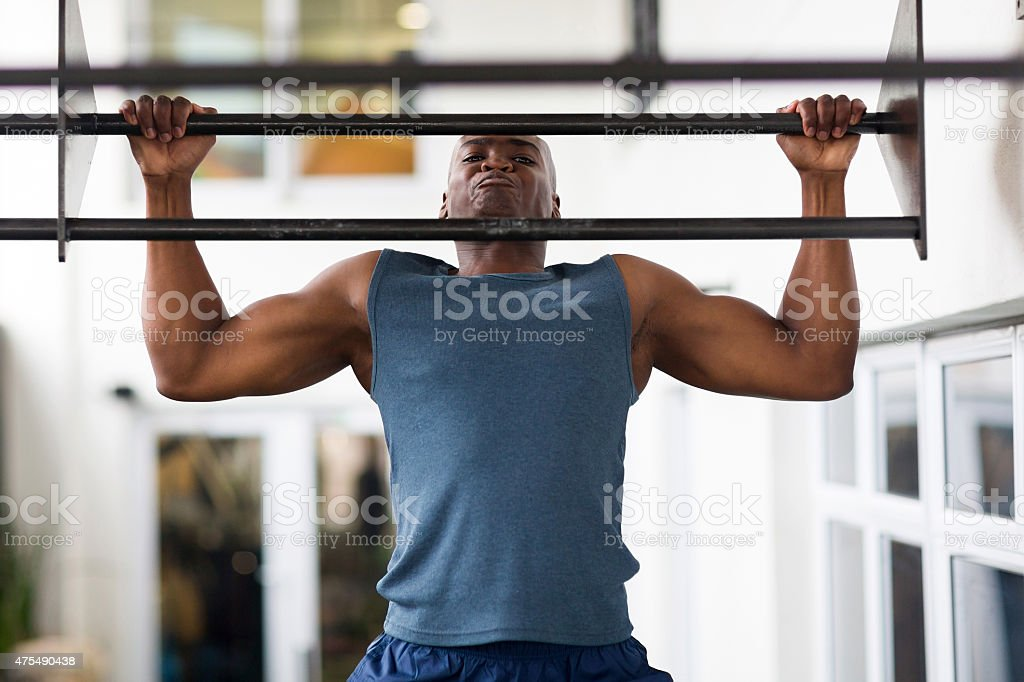 african man doing pull-ups on a bar stock photo