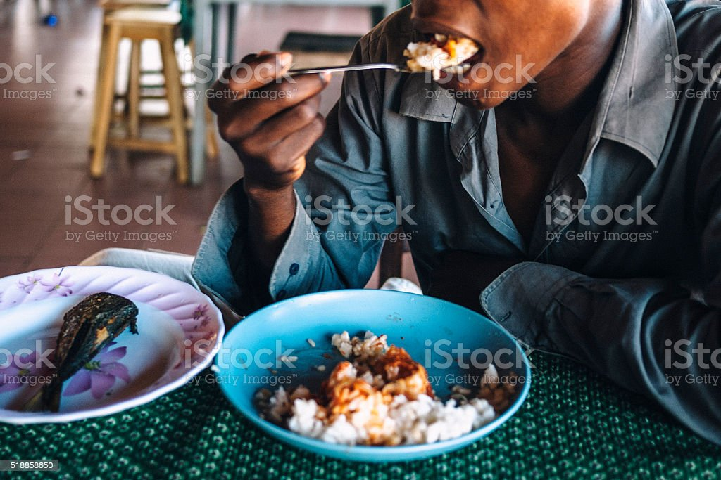 African man eating fish and rice with peppersauce. stock photo