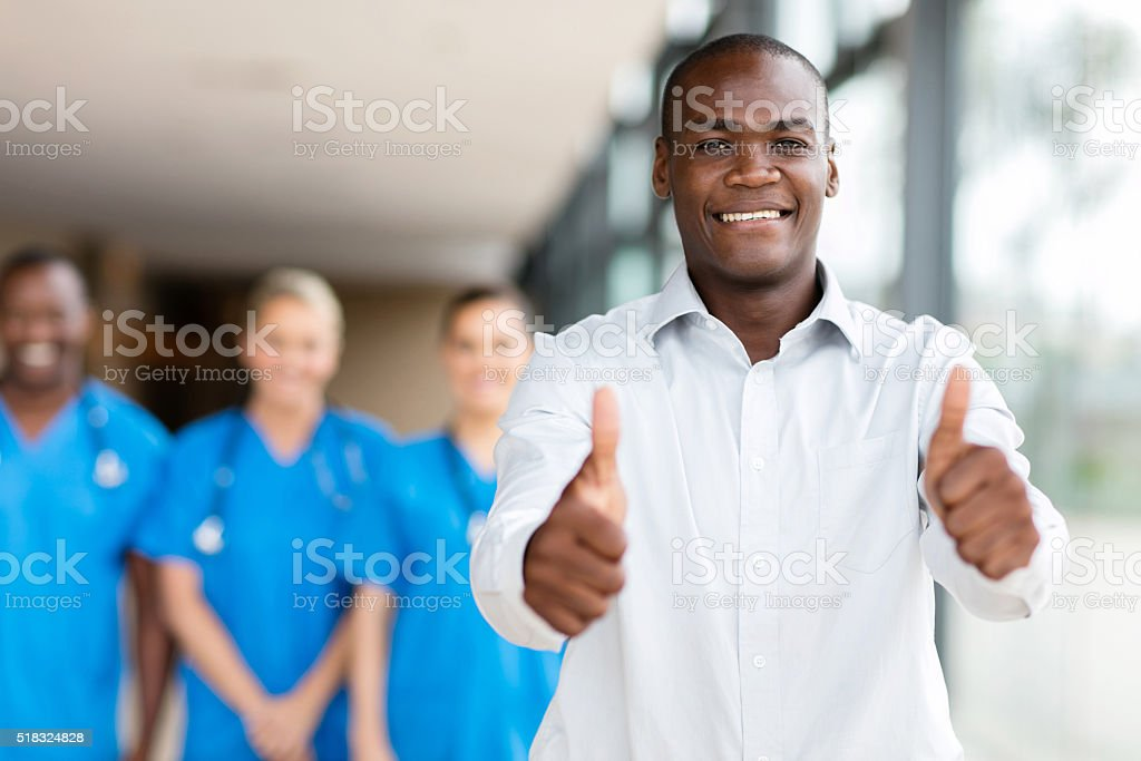 african man giving thumbs up stock photo