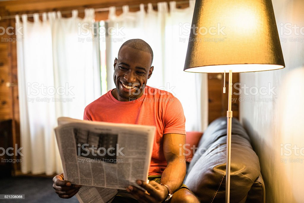 African man reading the newspaper on the living room stock photo