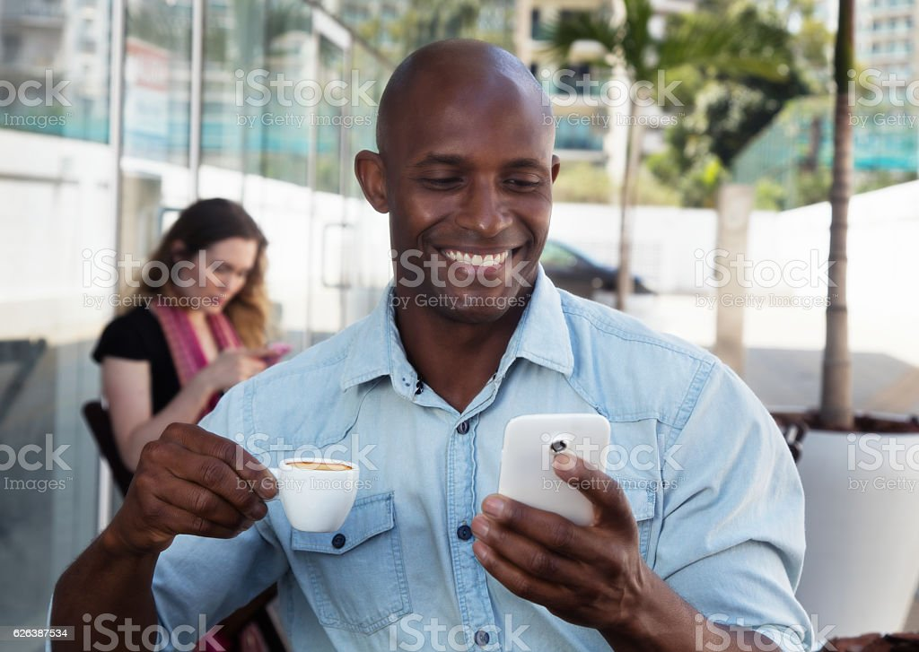 African man receiving message at phone in a restaurant stock photo