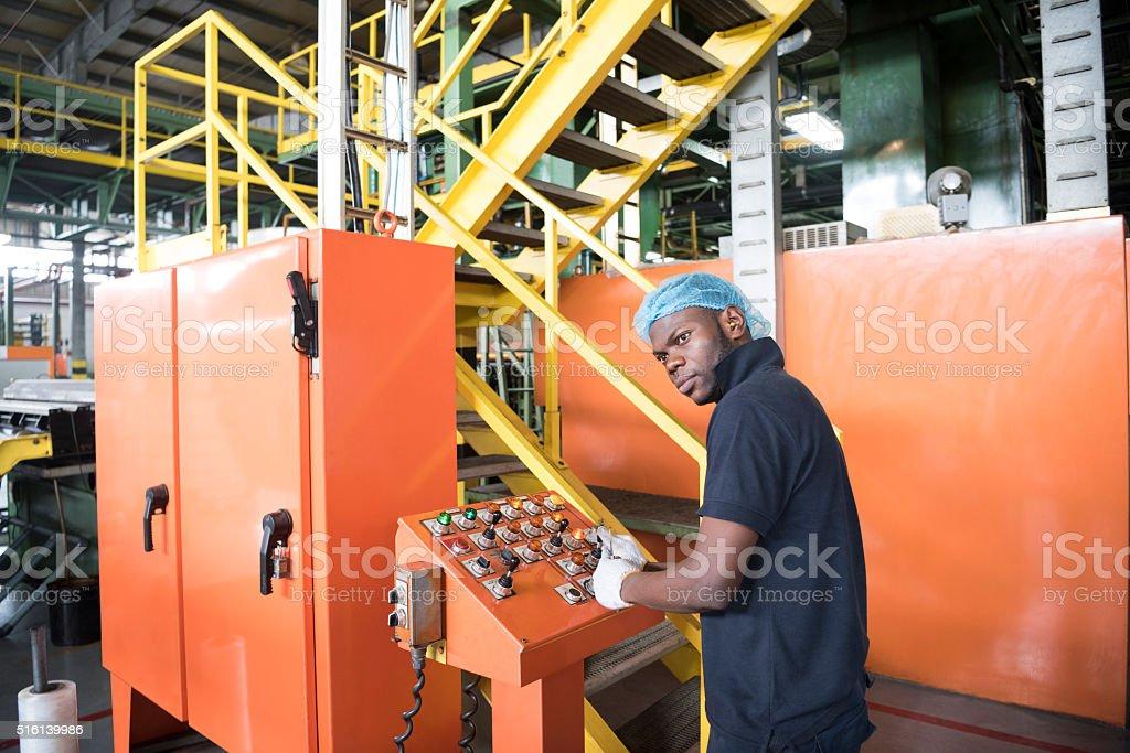 African man using control panel in aluminium processing plant stock photo
