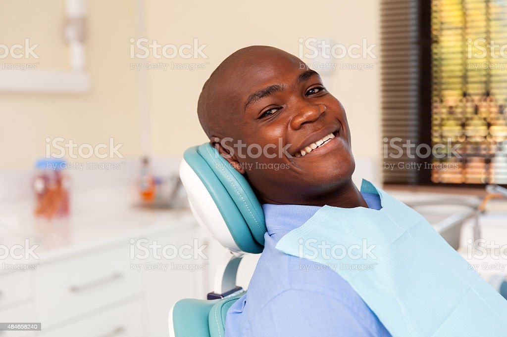 african man visiting dentist stock photo