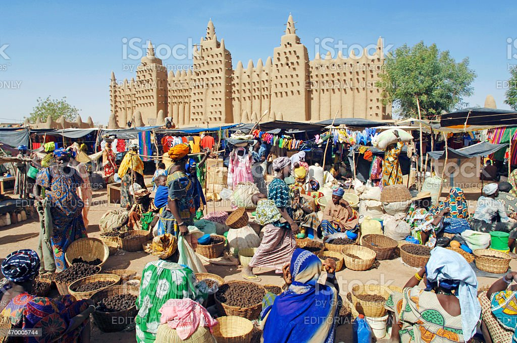 A busy and colourful market scene in front of the great mud Mosque in...