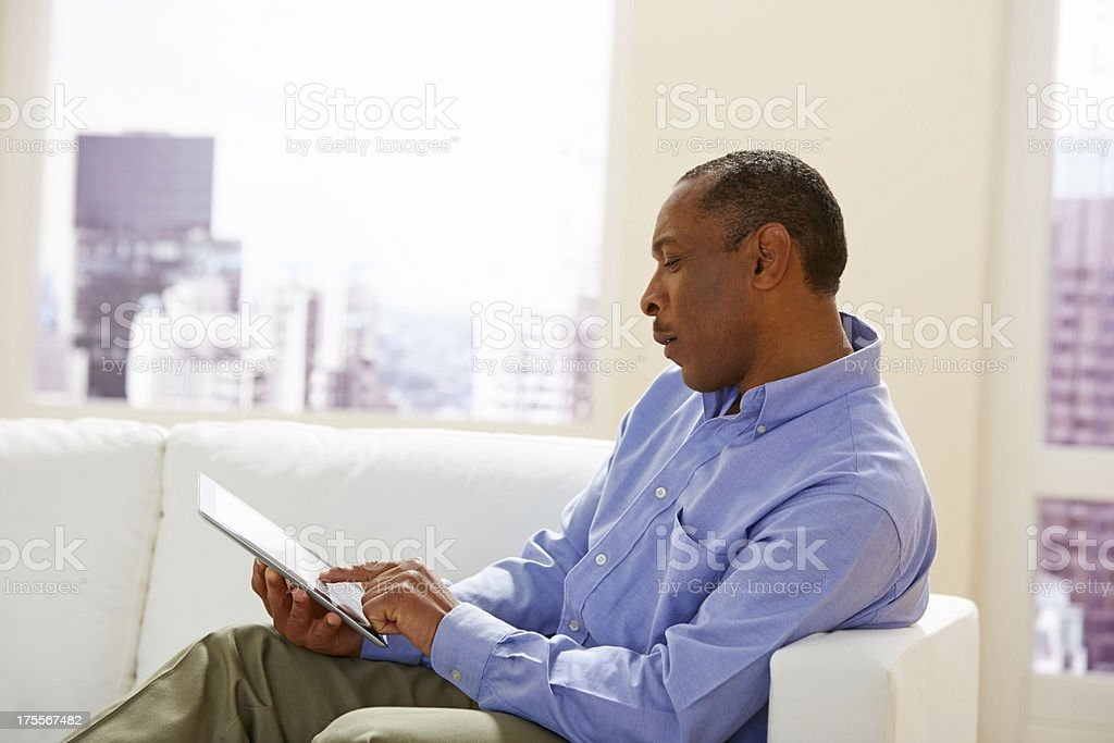 African mature guy working on digital tablet royalty-free stock photo
