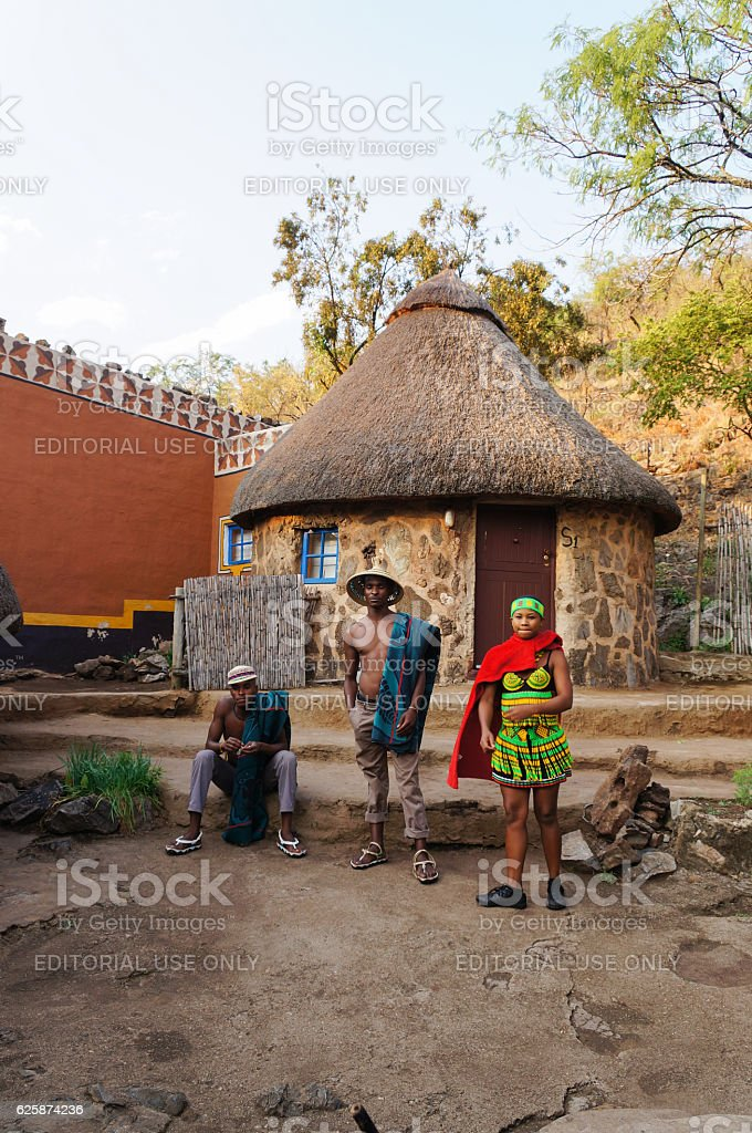 African men and woman standing in front of local hut . stock photo