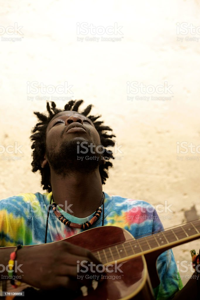 African musician playing guitar with eyes shut stock photo