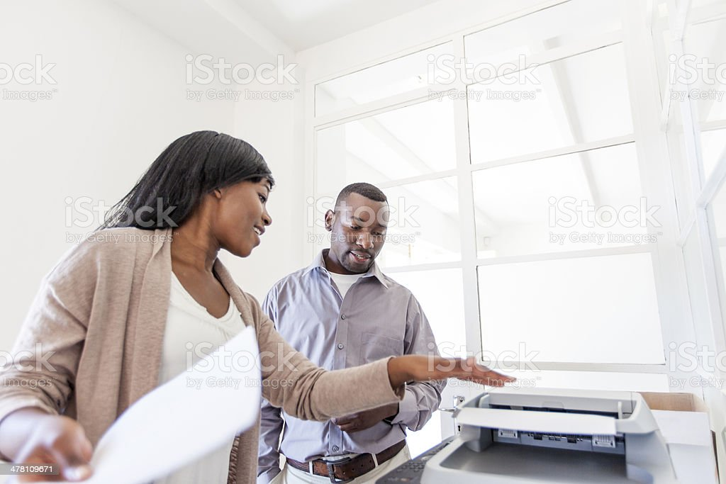 African office worker having a conversation at the printer stock photo
