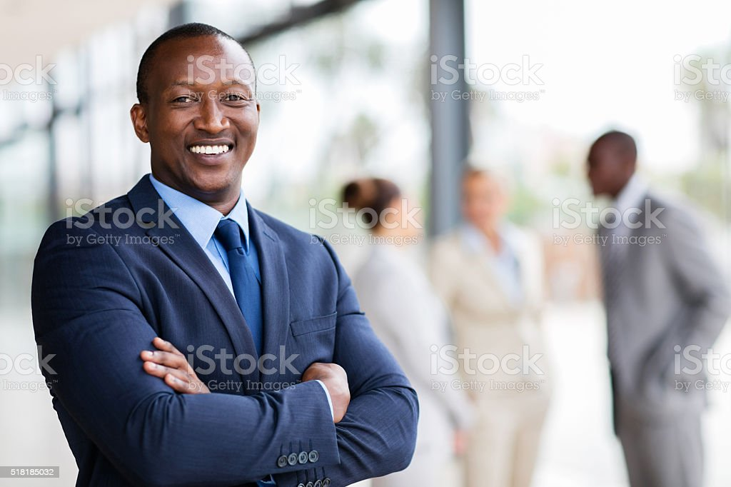 african office worker with arms crossed stock photo