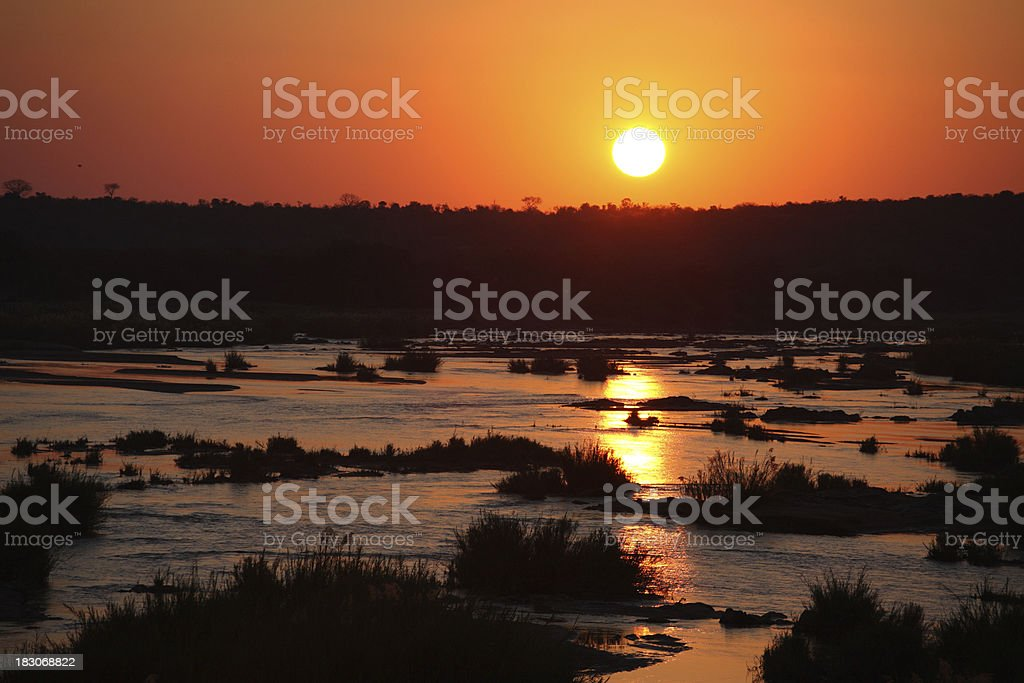 African river scenic sunset, with the sun just above horizon royalty-free stock photo