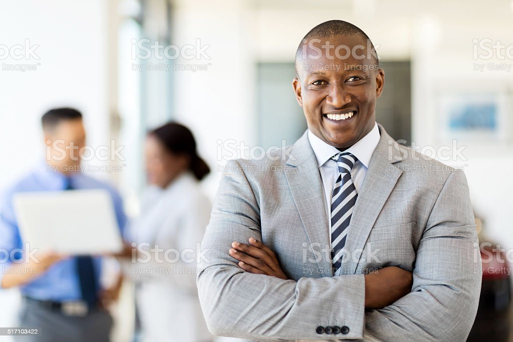african salesman standing at car dealership stock photo