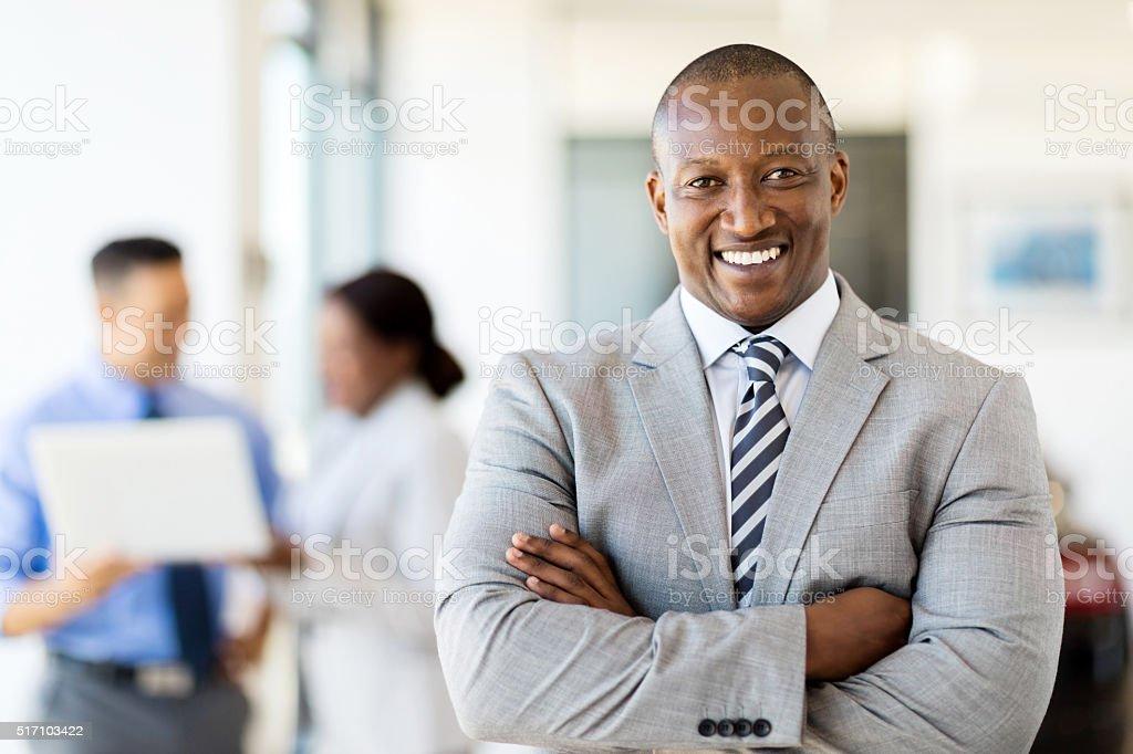 african salesman standing at car dealership stock photo