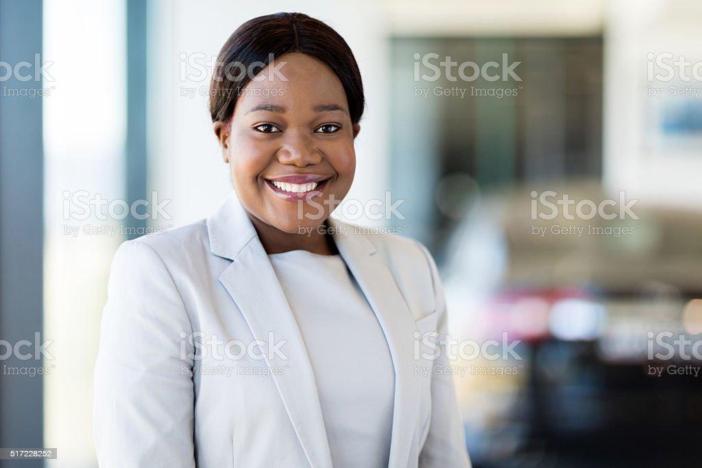 african saleswoman standing at car dealership stock photo
