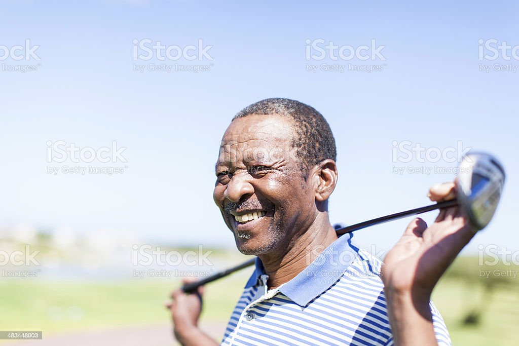 African senior golfer holding his club with a smile. stock photo