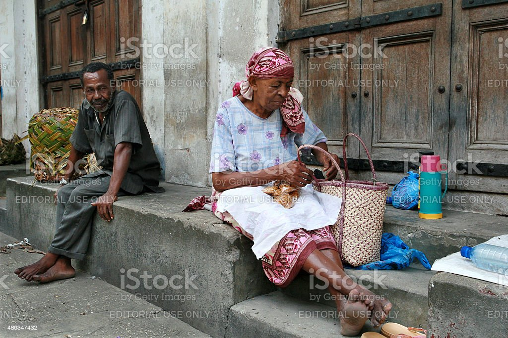 African street traders sit at the of closed Trade Rows. stock photo