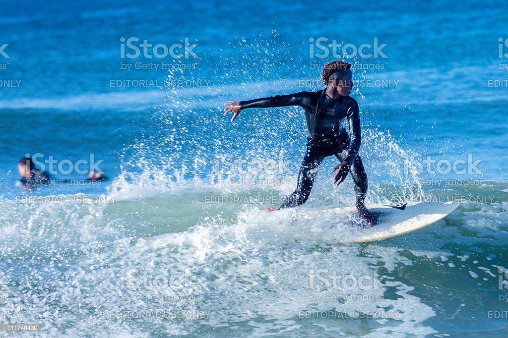 African teenager surfing a wave in Kommetjie beach stock photo