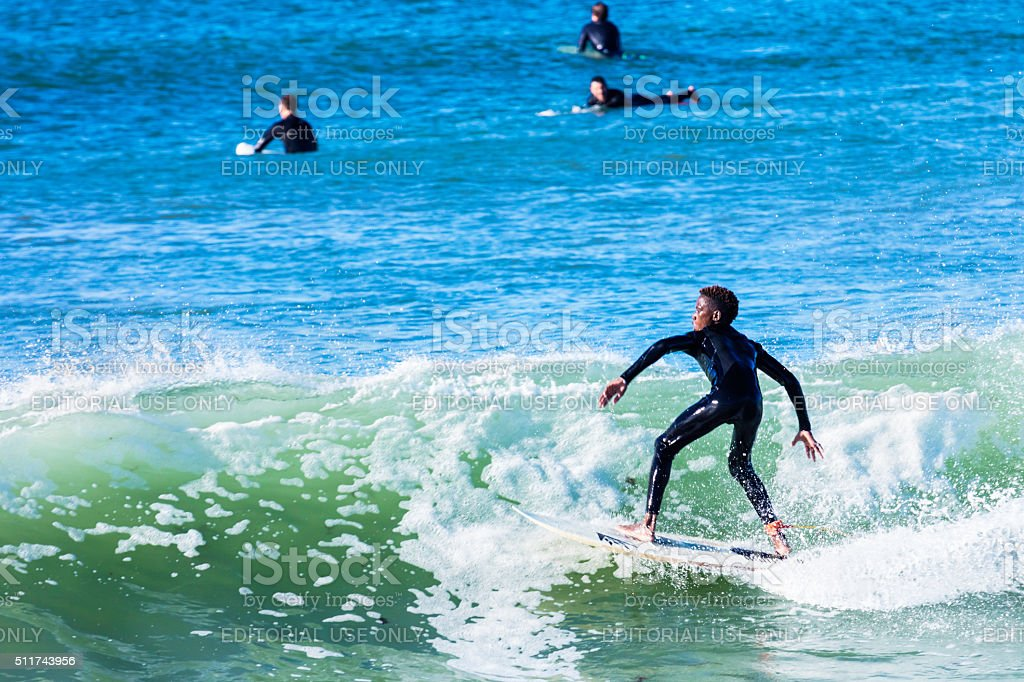 African teenager surfing  in Kommetjie beach stock photo