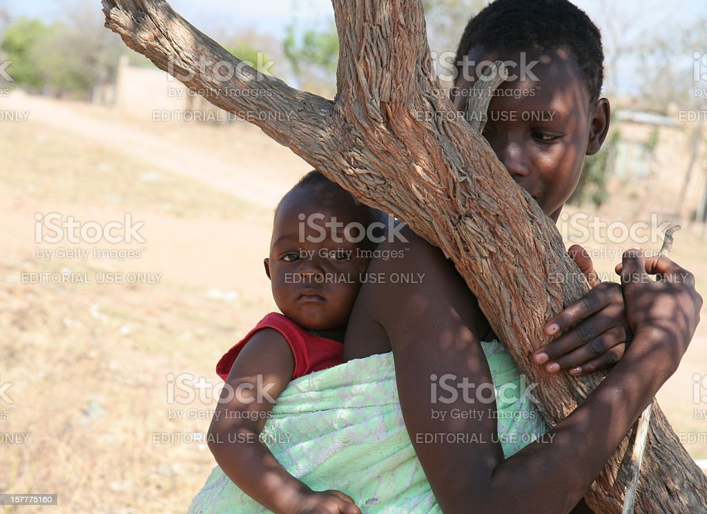 African woman and child in the shade of a tree stock photo
