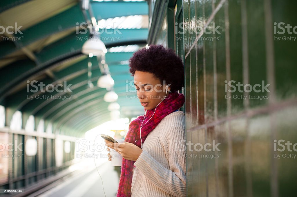 African woman at subway station waiting for the train stock photo