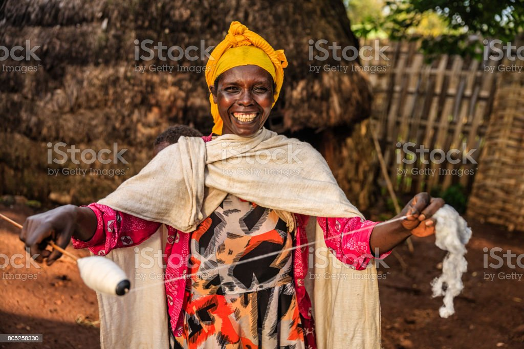 African woman carrying her baby and spinning wool, East Africa stock photo