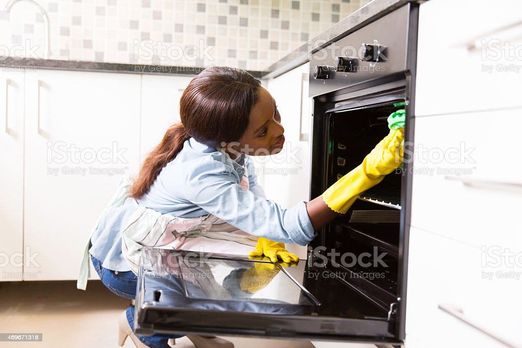 african woman cleaning in the kitchen stock photo