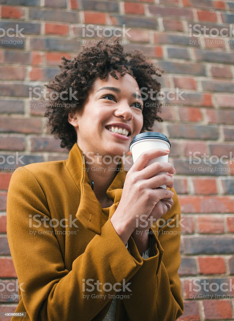 African woman drinking cofee in the park stock photo