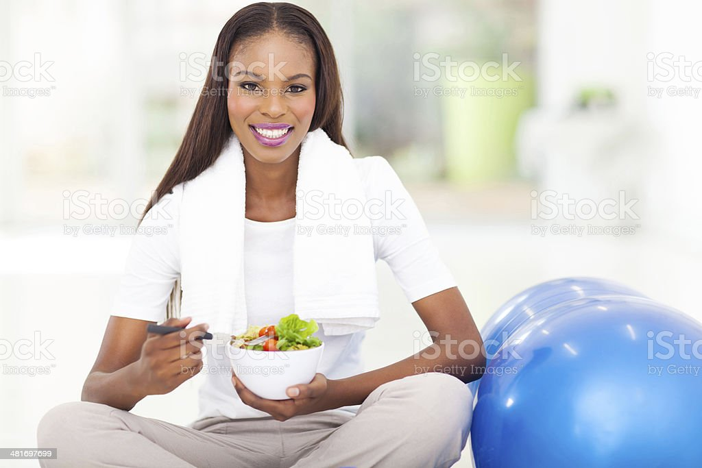 african woman eating healthy salad stock photo
