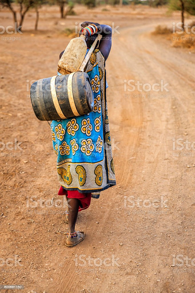 African woman from Maasai tribe carrying water, Kenya, East Africa stock photo