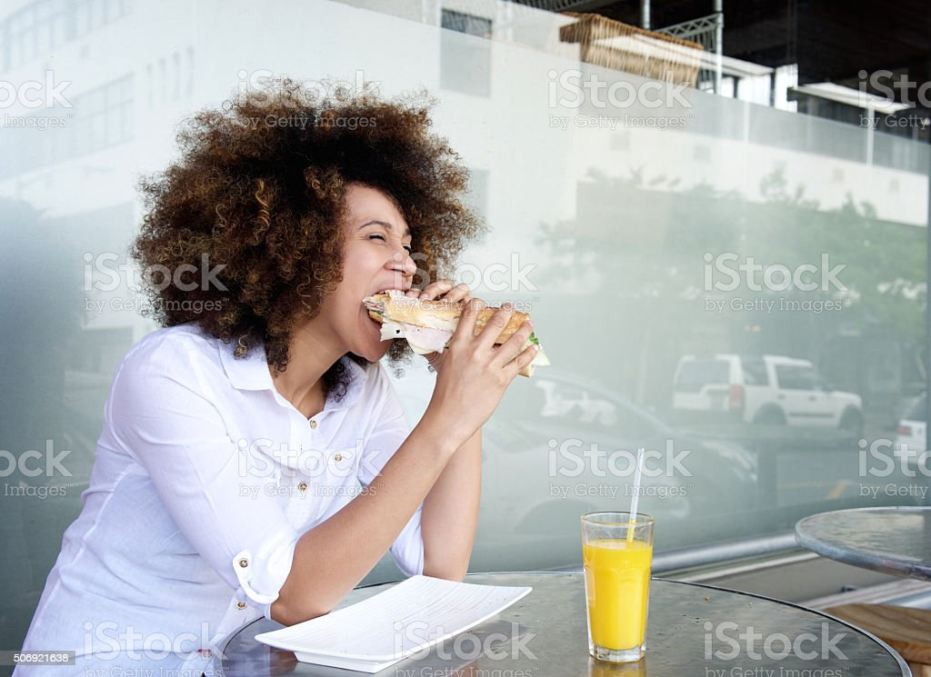 African woman in cafe eating sandwich stock photo