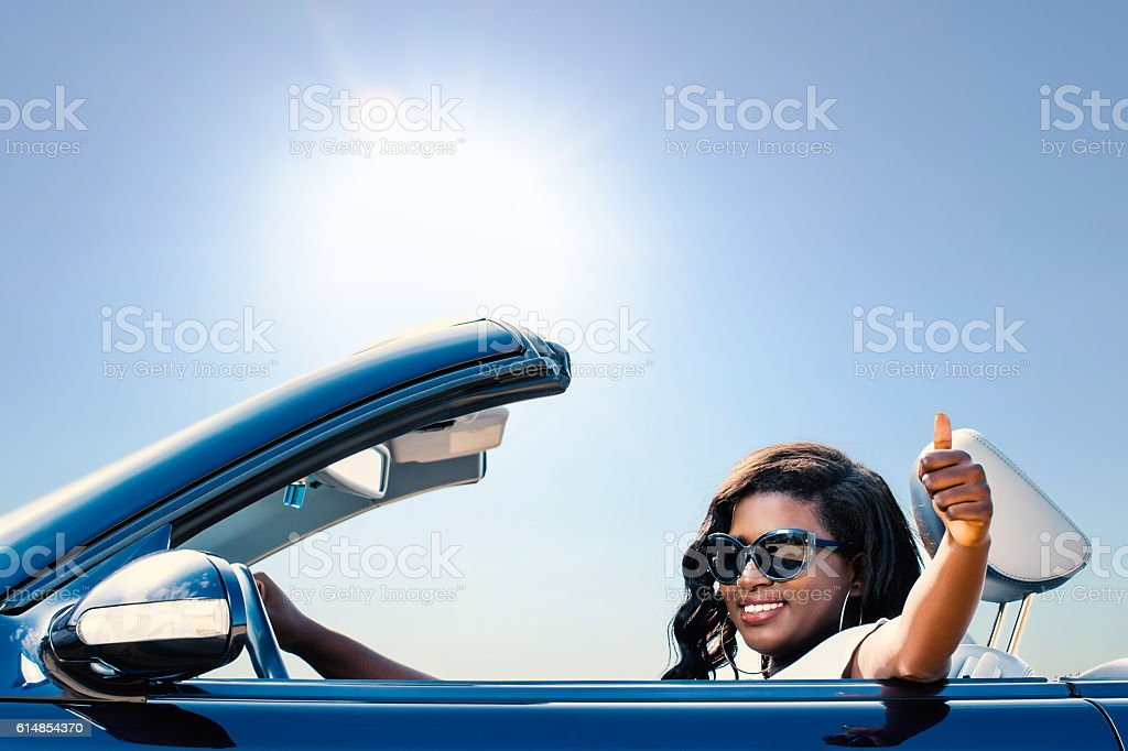 African woman in convertible doing thumbs up. stock photo