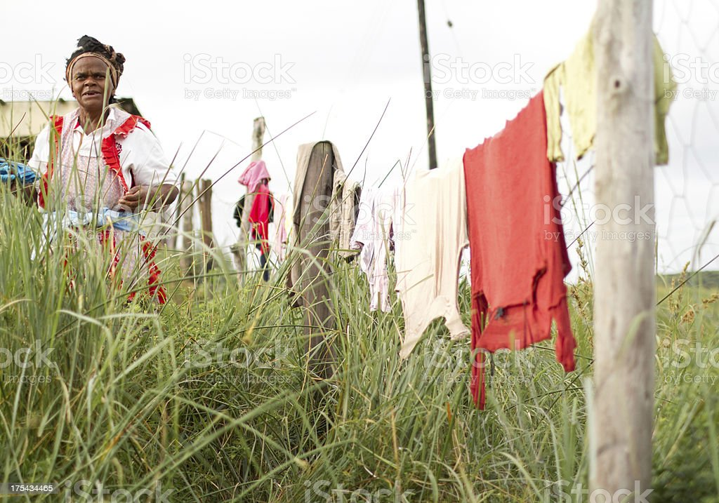 African woman in traditional dress hanging laundry stock photo