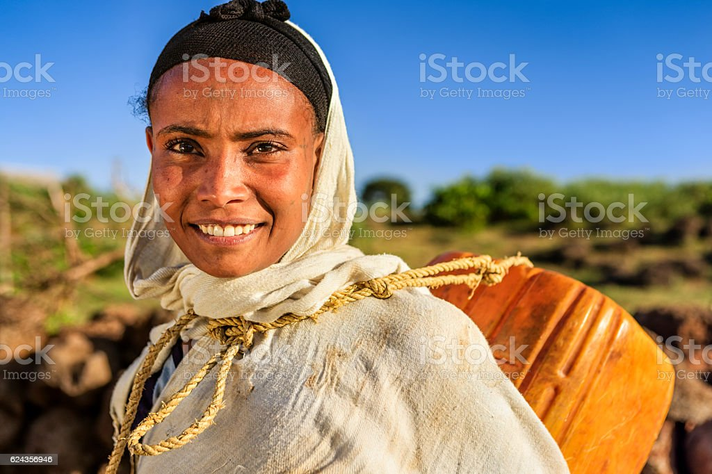 African woman is carring water to her house, Ethiopia, Africa stock photo