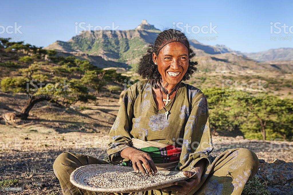 African woman is sifting the sorghum, East Africa stock photo